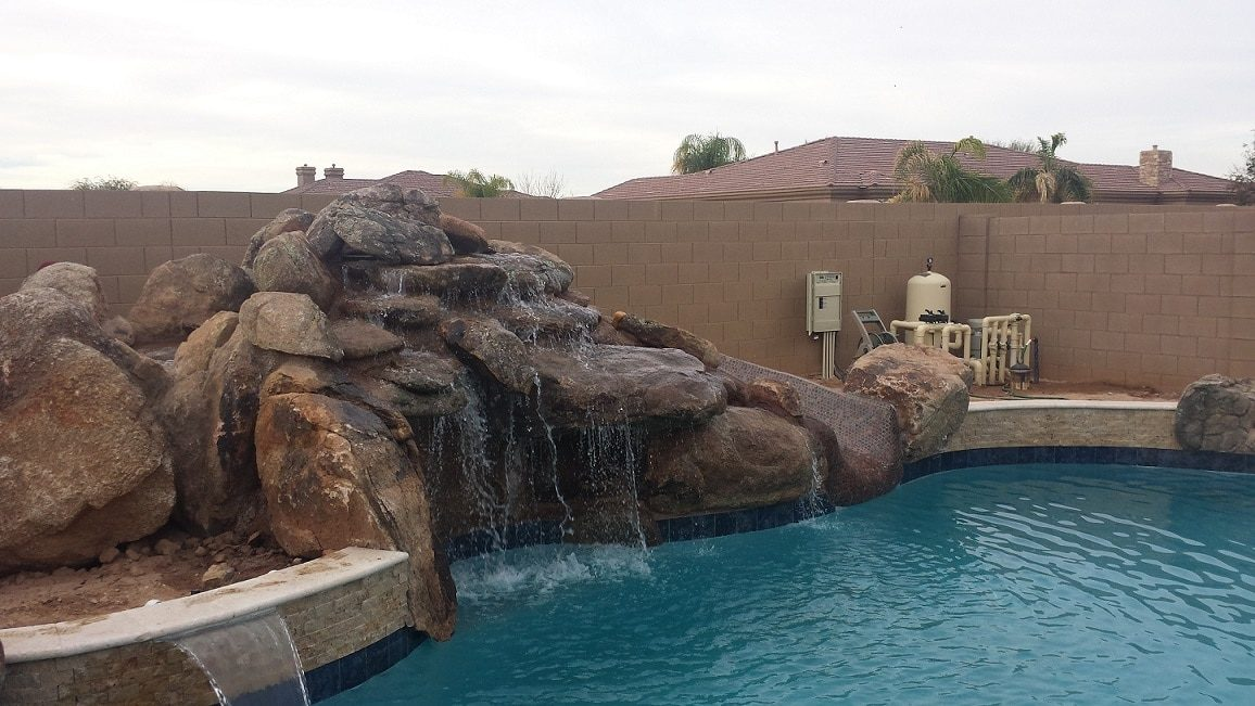 Gorgeous view of a new swimming pool built in Dallas, Texas. The swimming pool has also had a huge, rock waterfall implemented in the pool design.