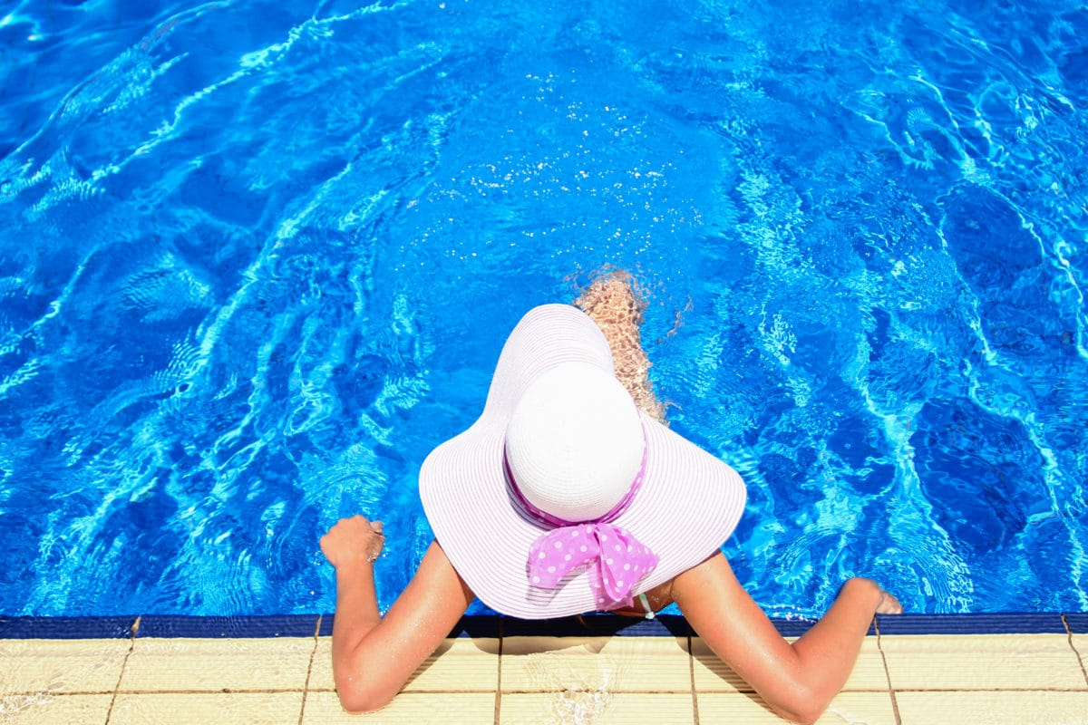 Woman sitting up against the pool wall wearing a white sun hat with a purple bow around it.