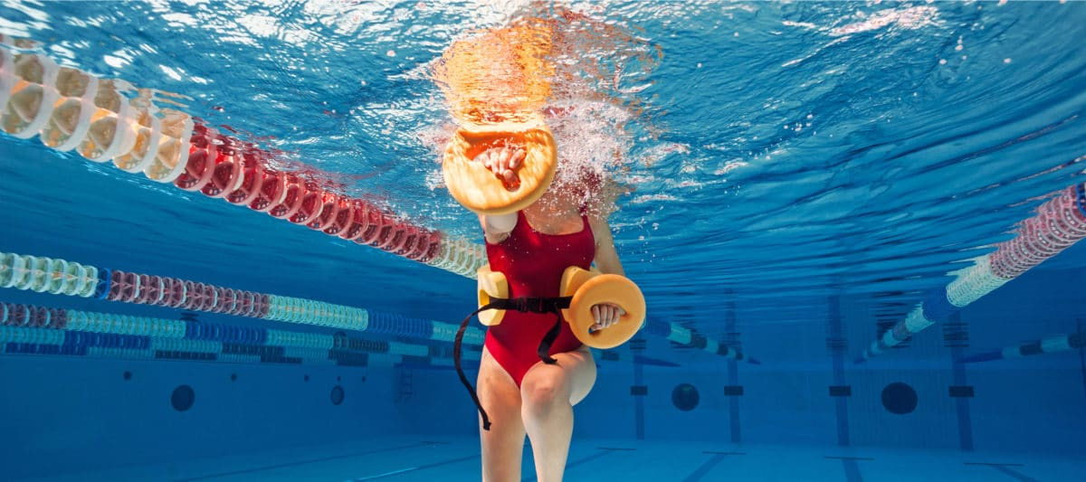 Woman wearing red swimsuit doing fitness exercises inside swimming pool.