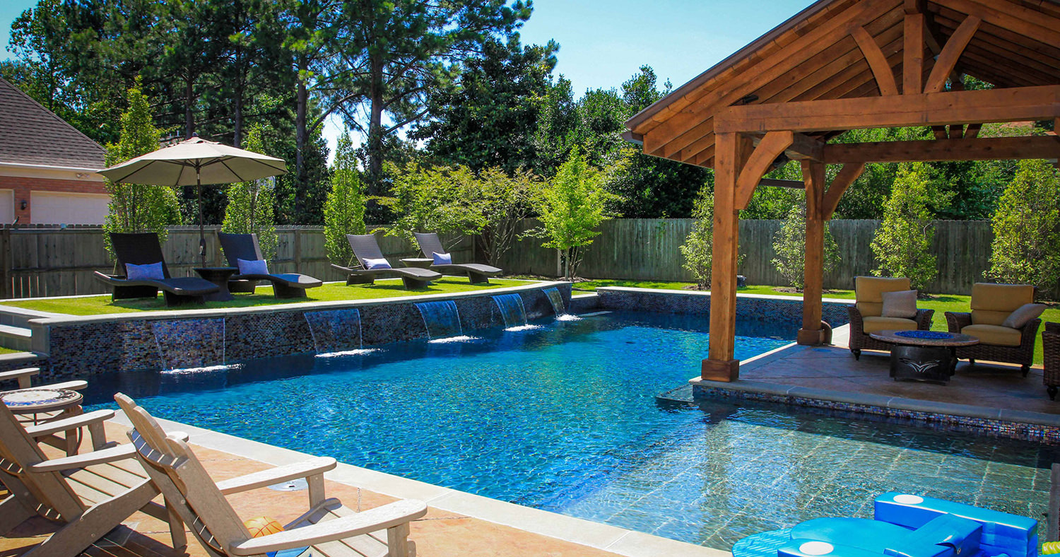 Swimming pool on a sunny day with a covered patio area for lounging.