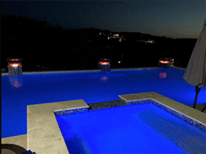 Gorgeous swimming pool at night time, pool lights are on, fire bowls around the pool.