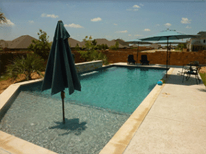 Huge swimming pool with an umbrella in the pool on the shallow end.