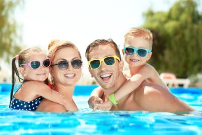 Middle aged mom and dad in the swimming pool. Little girl wearing glasses is on her moms back and a little boy wearing sunglasses is on his dad back. Having family time in their pool.