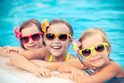 3 young girls having fun in a warm swimming pool.