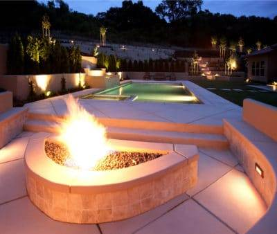 A lounge area next to the pool. Shows fire features and water features that compliment the new swimming pool. Water Features and Fire Features.