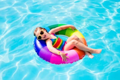 Happy little girl playing with colorful inflatable ring in outdoor swimming pool on hot summer day.