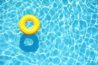 Sun shining down on crystal clear water in a swimming pool. Yellow Float.