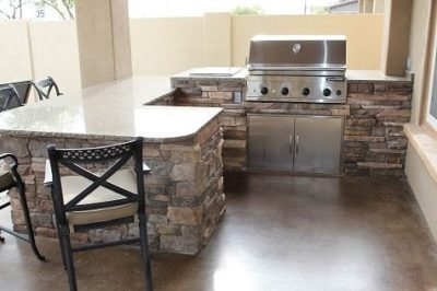 View of the Wright family's outdoor eating area. Bar with stools and a silver grill.