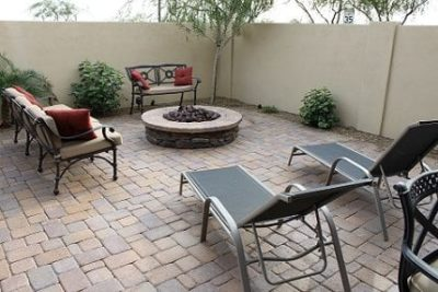 Phoenix, Arizona family showing their backyard sitting space that has a built in, circular fire pit with chairs all around it.