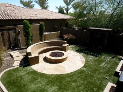 Chandler, Arizona family's backyard with a fire pit built in and a built in stone sitting area around the fire pit.