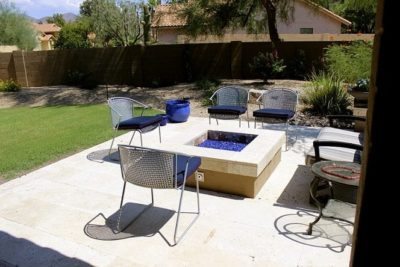 Beautiful sitting area on back patio with a square fire pit surrounded by chairs for lounging.