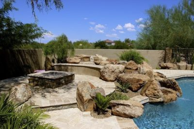 Family in Gilbert, Arizona sharing their back yard swimming pool that has a rock water fall draining into the pool. Behind the water fall is a built in, stone, square fire pit.