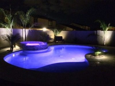 Night view of the Bernard Family swimming pool, purple lights turned on in the swimming pool and hot tub.