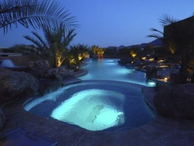 Night time view of hot tub over looking the swimming pool, pool and hot tub lights are turned on, lights shining up into the tree surrounding the swimming pool.