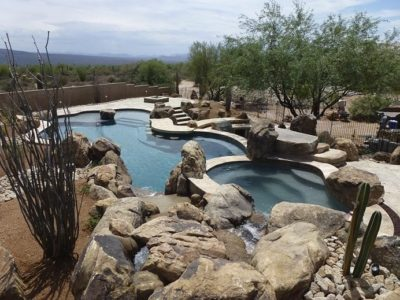 Full view of the Riley family's swimming pool, hot tub, and backyard.