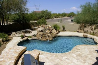 Perry family swimming pool in their backyard, rock waterfall flowing into the pool.