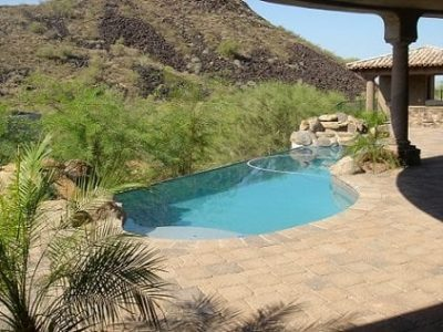 View of a swimming pool in a families backyard, background has trees and a mountain of rocks.