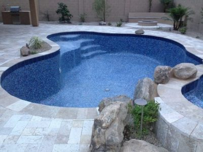 Close up, side view of a backyard pool, backyard grill in the background along with a fire pit.