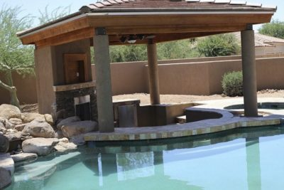 Family in Chandler, Arizona showing their beautiful swimming pool and the gazebo that has a sitting area and fireplace.