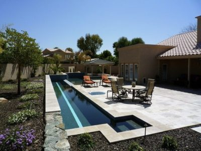 Drew family backyard with a small, narrow, swimming pool and a sitting area and a round table with chairs.