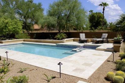 Side view of the Wilkinson family swimming pool, shows two lounge chairs next to the pool.