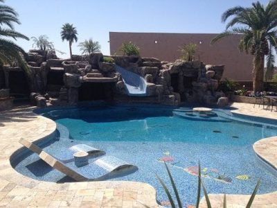 Luck family backyard swimming pool with a water slide surrounded by rocks. Beautiful swimming pool oasis, lounge chairs in built into the shallow end of the pool.