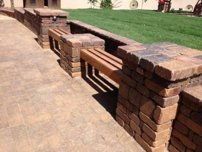 Brick wall landscaping with sitting area. Pavers on the ground area.