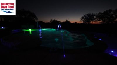 Swimming pool in Fort Worth, Texas at night time with green pool lights turned on.