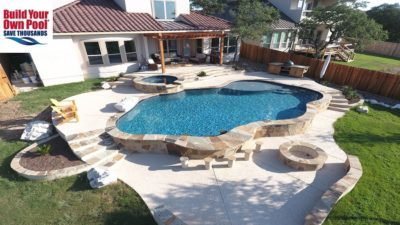 Zoomed out view of a backyard in Houston, Texas with a huge swimming pool, hot tub, and fire pit. Covered back porch area.