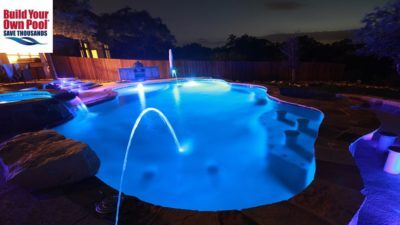Fort Worth, Texas swimming pool and hot tub with blue lights on, lights on stairs lit up, waterfall is flowing into the water.
