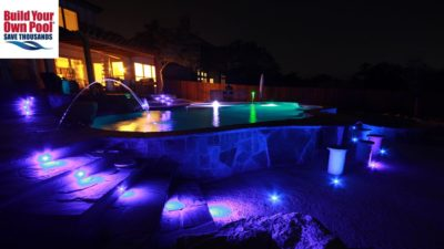 Fort Worth, Texas backyard with a swimming pool that is lit up with pool lights and there are ground lights surrounding the pool. Stairs are also lit up.
