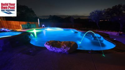 Fort Worth, Texas side view of the swimming pool, hot tub and water fall. Pool and hot tub have ice blue lights turned on at night time. Beautiful backyard.