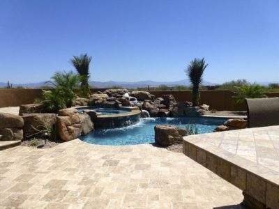 Gorgeous swimming pool design with rock waterfall flowing into the swimming pool. Located in Mesa, Arizona.