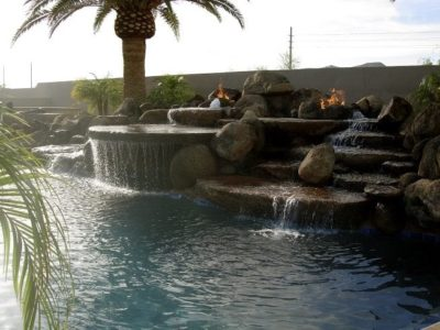 Phoenix, Arizona swimming pool with burning fire pits at the top of the swimming pool water fall.
