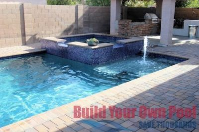 Gorgeous backyard swimming pool in Glendale, Arizona with a hot tub connected to the swimming pool. The swimming pool also has a small fountain coming up out of the swimming pool.