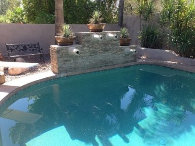 Swimming pool with brick wall that has spouts for water features. Swimming pool is located in Tucson, Arizona.