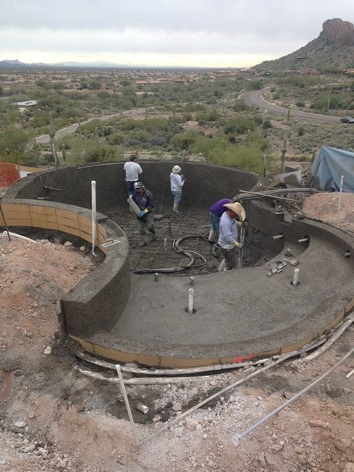 Men working to apply shotcrete to a newly built swimming pool in Texas.