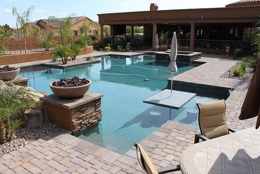 Gorgeous backyard swimming pool with fire bowls, water features, trees, patio furniture.