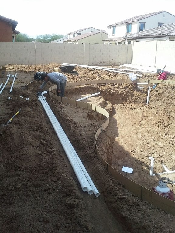 Up close view of a man working on a swimming pool plumbing system for a pool that is being built in Phoenix, Arizona.