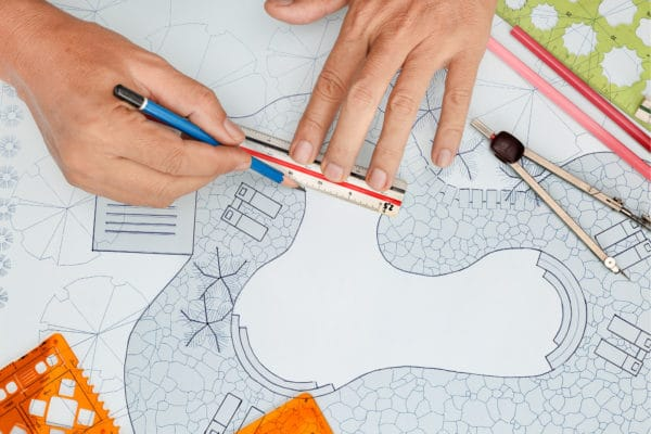 Person drawing a swimming pool design on a piece of paper with a pencil.
