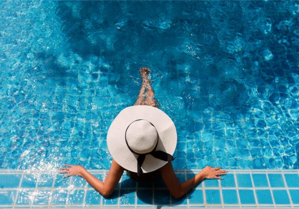 Young woman with brown hair, wearing a tan sun hat with a black bow on it, relaxing in a swimming pool.