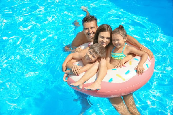 Happy family with inflatable ring relaxing in swimming pool.