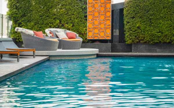 Beautiful backyard pool with crystal clear water, two large and round chairs to lounge on.