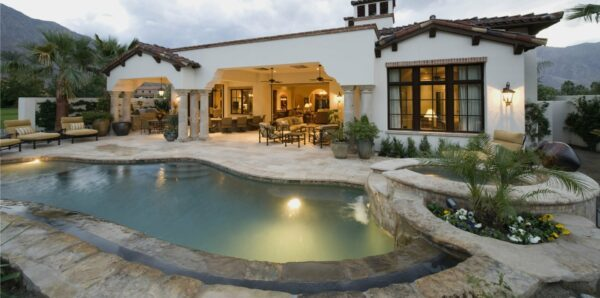 Luxurious backyard swimming pool after being built, shows covered patio with furniture and the pool lights are on.