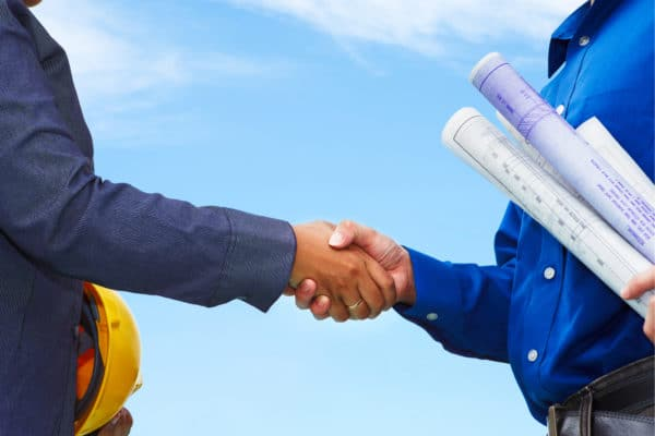 Contractor shaking hands with a client who is holding swimming pool drawings.