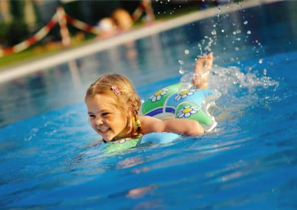 Happy little girl splashing around on a float in the swimming pool.
