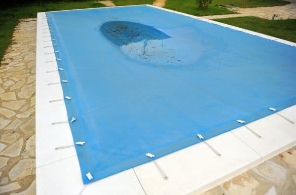 Swimming pool protected with a blue tarp in autumn.