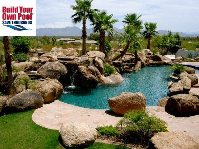 Backyard swimming pool surrounded by sunshine, giant rocks and trees. Build Your Own Pool Logo in top left hand corner.
