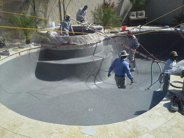 A view of men working on building a swimming pool for a family in Austin, Texas. The photo shows the men working on the swimming pool surface and getting the pool building process completed.