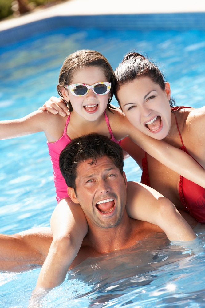 Happy mom, daughter, and dad in a swimming pool. Little girl is on her dads shoulders.
